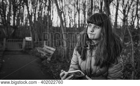 Cinematic Portrait, Person Girl Woman Standing In The Park With Mobile In Hands, Black And White Ima