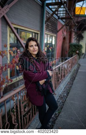 Beautiful Woman Leaning Against A Pink Handrail In The Street