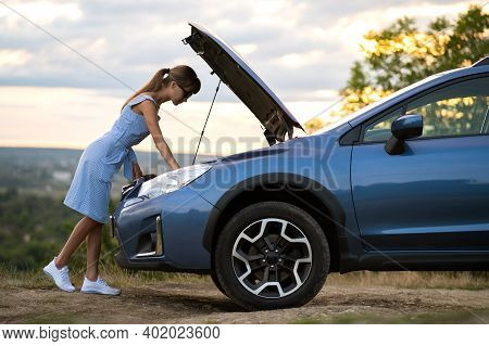 Stranded Young Woman Driver Standing Near A Broken Car With Popped Up Bonnet Inspecting Her Vehicle