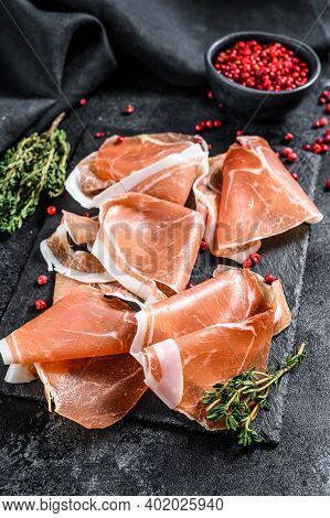Spanish Jamon Serrano With Thyme, Cured Ham. Black Background. Top View