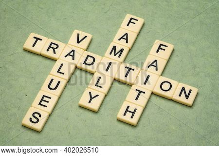 values, tradition, family and faith  crossword in ivory letter tiles against textured handmade paper, culture, religion and lifestyle concept