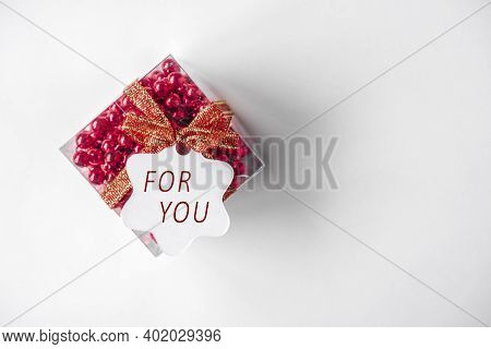 Red Gift Box With Red Ribbon, Red Beads, Bow. White Paper Tag With Text For You, Isolated On White B