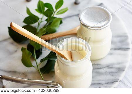 Two Portions Of Fresh Natural Organic Yogurt In A Glass Jars On Marble Tray. Homemade Greek Yogurt W