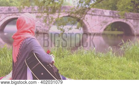 Muslim Girl Playing Guitar And Looking Towards The Bridge. Relaxing While Sitting On The River Bank