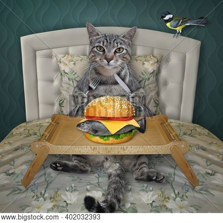 A Gray Cat Is Eating A Big Fresh Fish Burger From A Wooden Tray In The Bed At Home.