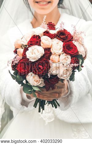 Bride With A Wedding Bouquet In Her Hands. Wedding Bouquet Close Up. Roses
