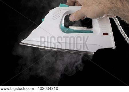 A White Iron Held In A Male Hand. Steam Escaping From The Ironing Machine.