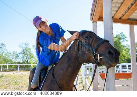 Girl After Equestrian Training Joyfully Looks At The Horse's Face