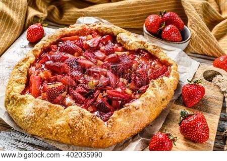 Galette With Strawberry And Rhubarb. Homemade Tart, Tarte. White Wooden Background. Top View