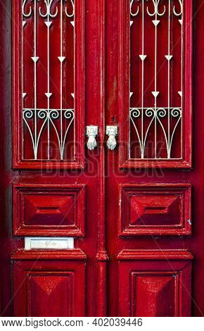Two knockers on a red door and a hand knocking with one of them. Lagos, Portugal