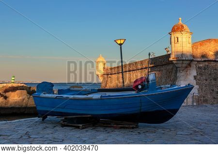 Boat near medieval Forte de Bandeira at sunset in Lagos Portugal