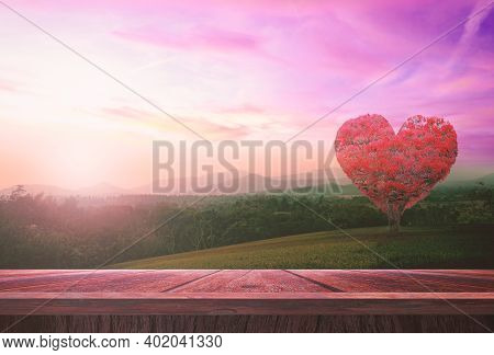World Health Day Concept: Wooden Table And Heart Shape Of Red Big Tree On Mountain Sunset Background