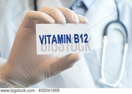 Doctor Holding A White Paper Card With Text Vitamin B12, Medical Concept. Healthcare Conceptual For