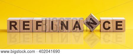 Refinance Word Written On Wood Block. Refinance Word Is Made Of Wooden Building Blocks Lying On The