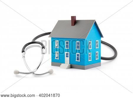 House model with stethoscope on white background. Family health concept