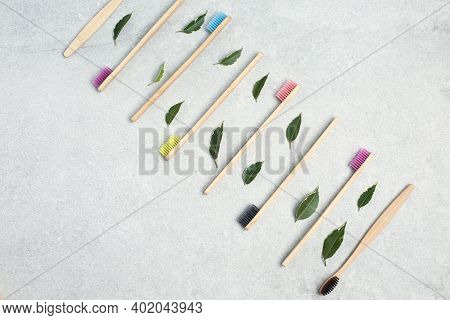 Bamboo Toothbrushes And Green Leafs On Stone Table