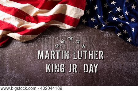 Happy Martin Luther King Day Anniversary Concept. American Flag Against Dark Stone Background