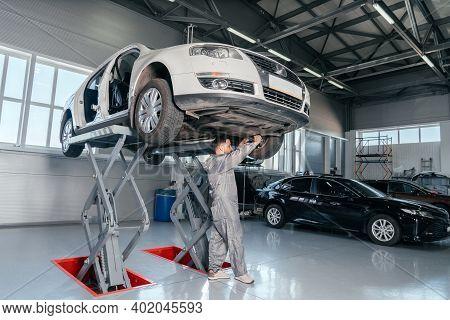 Mechanic Repairing Car On Lift In Mechanic Shop Or Garage, Interior Of Auto Repair Workshop