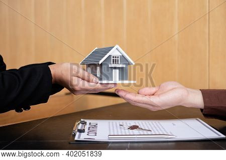 A Real Estate Agent Gives The House To A New Owner's Client After Completing The Signing Of The Leas