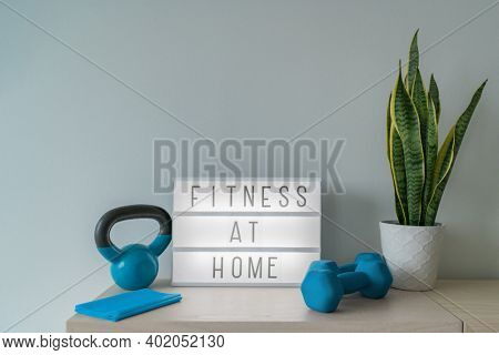 Fitness at home light sign with kettlebell weight and dumbells, resistance bands for pilates online class. Exercise indoors for women.