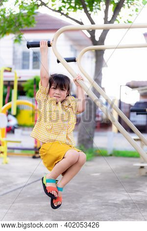 Portrait Active Girl Plays In The Hanging Bar. Children Are Exercising. Child Play In The Playground