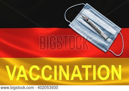 Covid-19 Vaccination In Germany Concept With Face Mask And Syringe Needle Vaccine On German Flag.