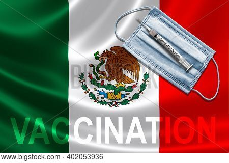 Covid-19 Vaccination In Mexico Concept With Face Mask And Syringe Needle Vaccine On Mexican Flag.