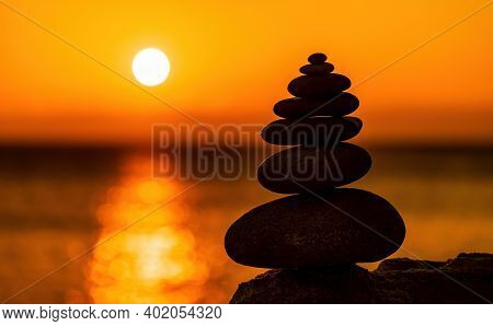Balanced Pebble Pyramid Silhouette On The Beach On Sunset. Selective Focus Abstract Bokeh With Sea O