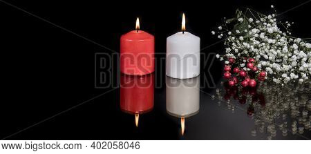Burning Candles, White Flowers And Red Berries On Black Background. Reflection In Dark Glass. The Co