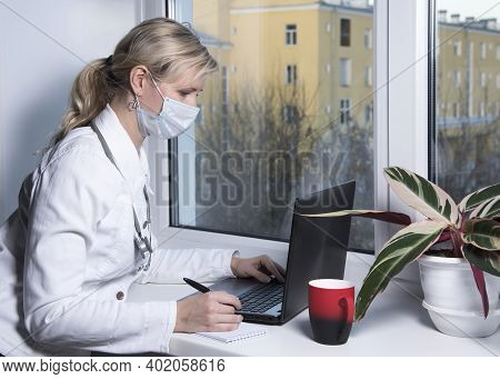Doctor Works Online. Physician Working At Notebook Remotely From Home Using Computer And Drinking Co