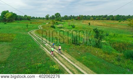 Family Cycling On Bikes Aerial View From Above, Happy Active Mother With Children Have Fun Outdoors