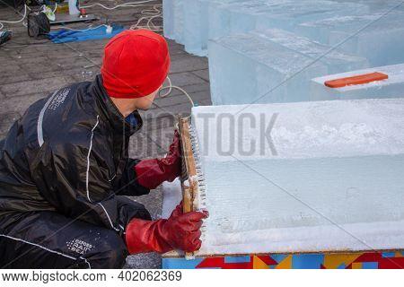 Lviv, Ukraine - January 02, 2021 : An Artist Making Ice Sculpture During Christmas Holidays Festival