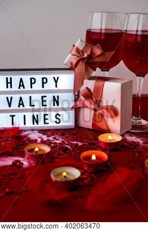 Lightbox With Text Happy Valentines Two Glasses Of Red Wine And Gift Boxes Burning Red Candles On Co