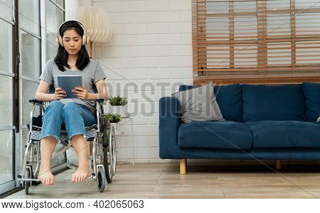 Happy Disabled Asian Woman Sitting In A Wheelchair And Working With Tablet At Home, The Concept Of T
