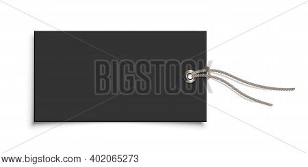 Empty Paper Black Clothing Label With Metallic Rivet And Grey Ribbon On White Background. Blank Tag