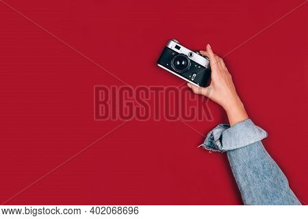 Female Hand Holding Old Retro Photo Camera On Red Background With Copy Space For Text. Trendy Vintag