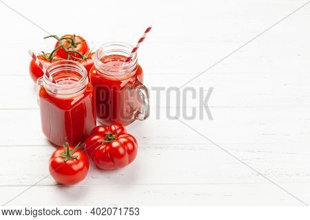 Fresh tomato juice and ripe tomatoes on wooden table. With copy space