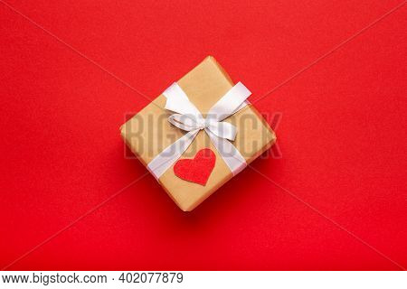 Gift With White Ribbon And Heart On Red Background. Women's, Birthday, Valentine's Day. Copy Space,