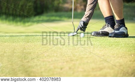 Close Up Hand Asian Woman Putting Golf Ball On Tee With Club In Golf Course On Sunny Day For Healthy