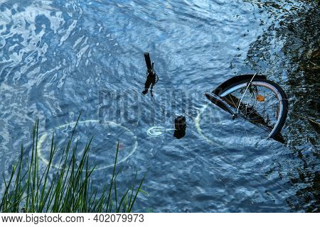 The Bicycle Drowned In The River. A Detail Of The Abandoned Or Stolen Bike.