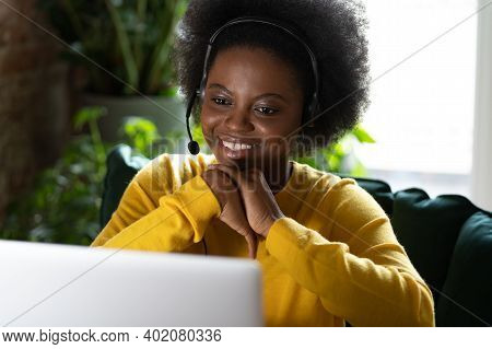 Smiling African American Millennial Woman Wear Headphones Talking In Video Chat, Using Laptop, Study
