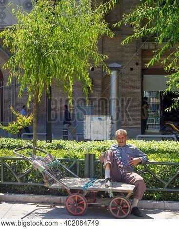 Tehran, Iran - May 22, 2017: Man Sitting On An Empty Cart On The Street Of Tehran. Iran's Unemployme