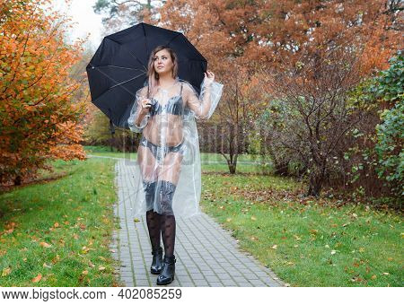 Young Woman In Black Lingerie, Stockings And A Transparent Raincoat With Umbrella Standing On The Al