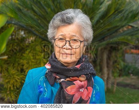 Portrait Of An Elderly Asian Woman Wearing Glasses, Smiling, And Looking At The Camera While Standin