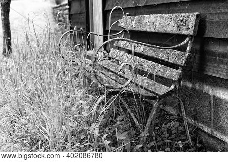 Old Bench Decaying Against An Old Shed In A Rural Garden. Black And White Monotone Landscape