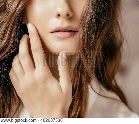 Beautiful Woman Applying Cosmetics With Her Hand On Face, Natural Look And Wavy Long Hairstyle, Beau