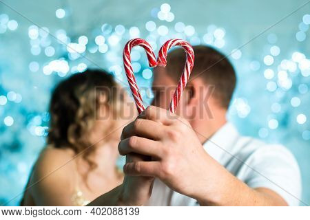 Couple In Love Kissing And Heart Made Of Two Lollipop. Valentines Day. Hands Hold Two Candy Canes Ma