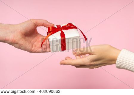 Man And Woman Hands Holding Gift Box With Red Bow On Pink Background, Close-up. Pastel Colors, Copy