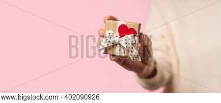 Beauty Woman Hands Holding Gift Box With Red Heart On Pink Background, Close-up. Pastel Colors, Copy