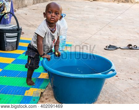 Mbour, Senegal - December Circa, 2020. African Baby, Less Than One Year, Wanting Bathing In A Basin